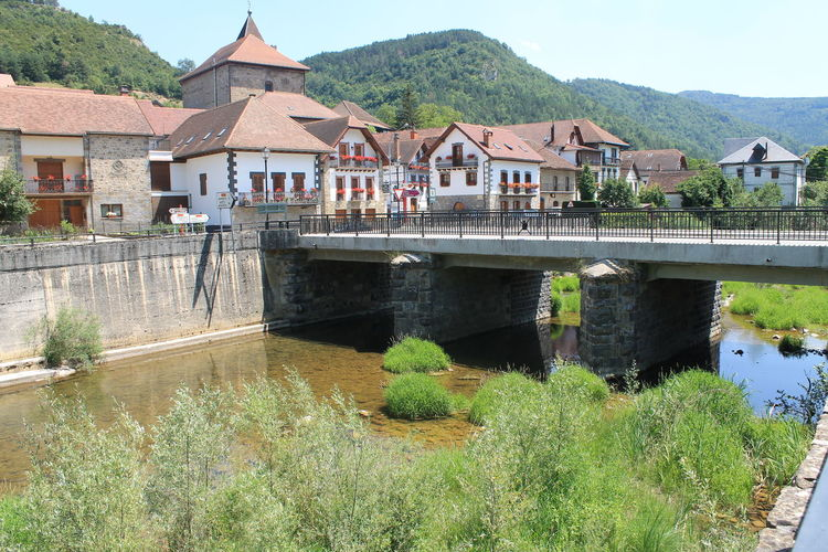 Bridge over river by houses and buildings against mountain