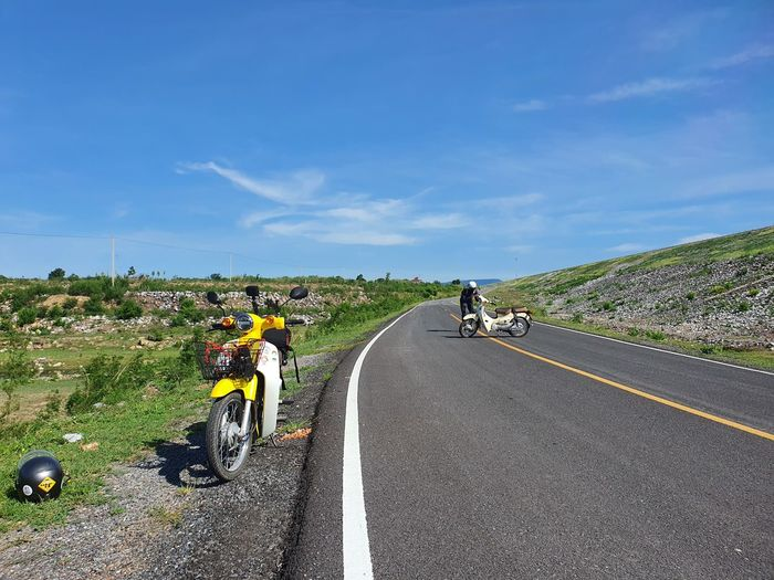 People riding motorcycle on road against sky