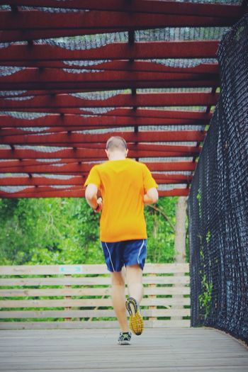 Rear view of man jogging on footbridge