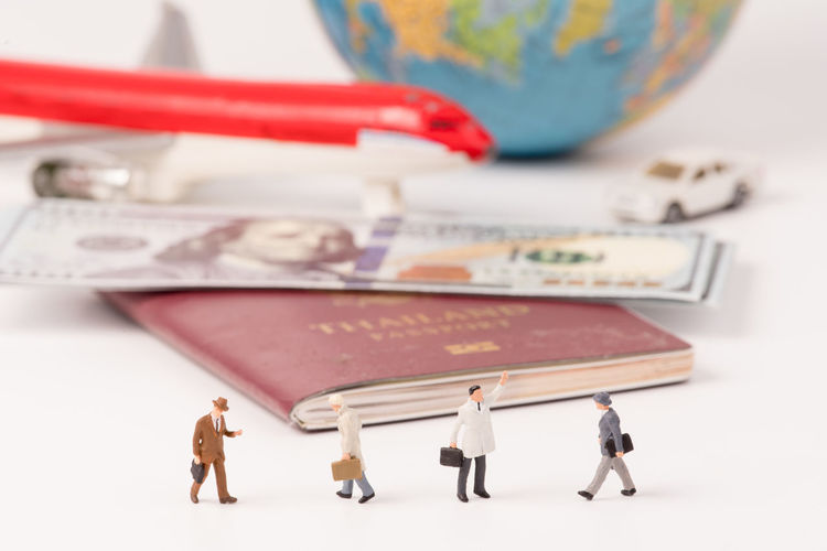 Close-up of figurines with passport and currency on table