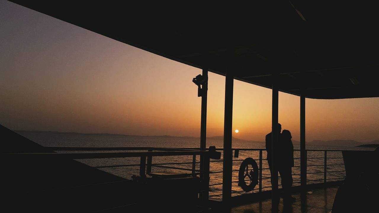 sea, silhouette, sunset, water, railing, real people, standing, nature, horizon over water, men, sky, two people, beauty in nature, scenics, leisure activity, outdoors, fishing pole, clear sky, full length, architecture, day, people