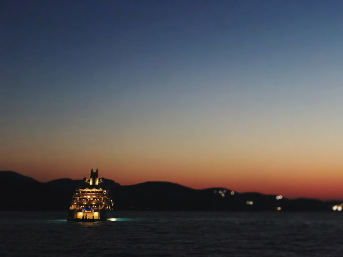 Illuminated ship sailing in sea against sky during sunset