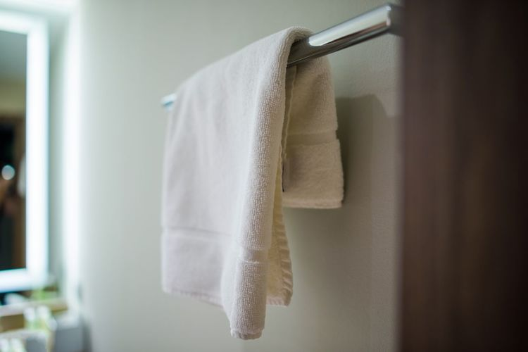 White Towel Hanging From Metal Rod In Bathroom