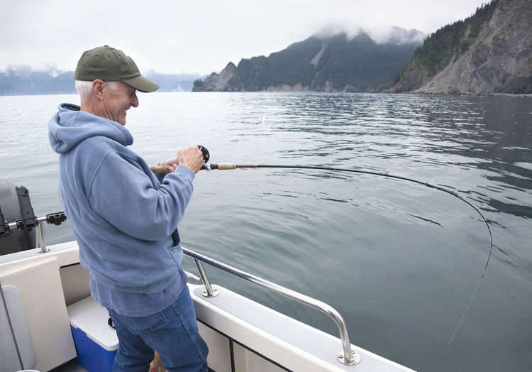Smiling senior fisherman reels in a salmon in the ocean near Seward, Alaska Fisherman Salmon Ocean Alaska Smiling Senior Man Fun Fishing Happy Fishing Rod Reel Catching Fish Cloudy Overcast Seward USA Outdoor Activity Recreational Pursuit Hills Trees Bay Color Image Photography Senior Adult Real People One Person