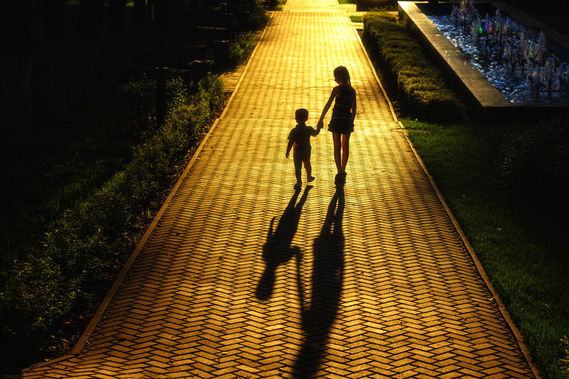 High angle view of people walking on footpath at night