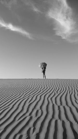 Girl With Umbrella Standing At Desert Against Sky