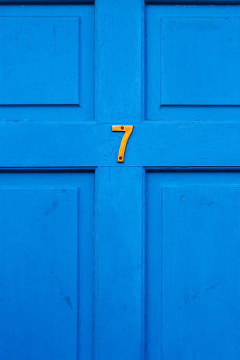 House number 7 on a blue wooden front door in london