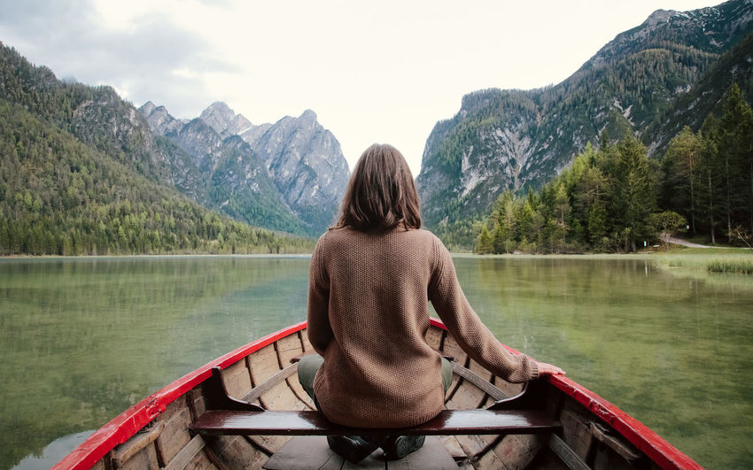 Rear view of woman boating on lake against mountains