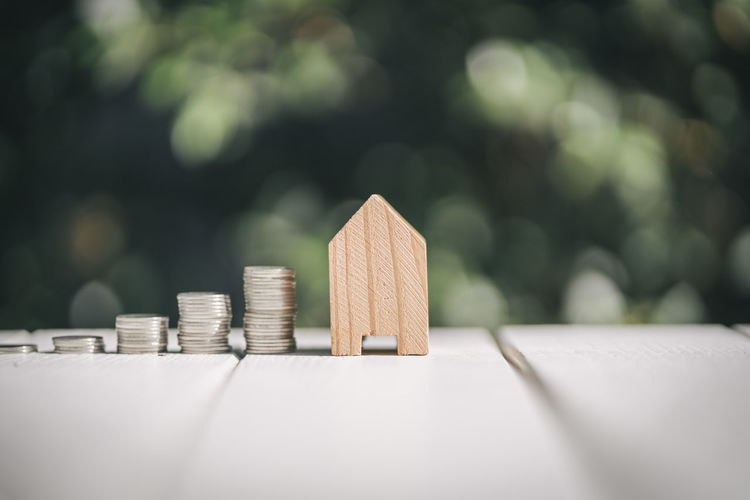 Close-Up Of Coins With Model Home On Wooden Table