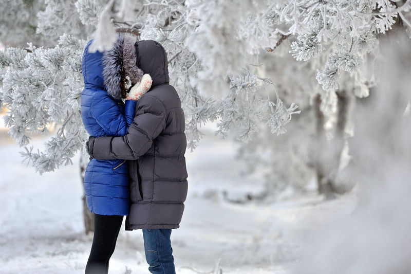 Side View Of Couple Hugging IN The SNOW