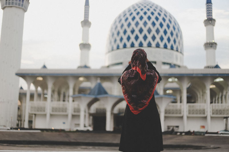 Rear view of young woman standing outside mosque against clear sky