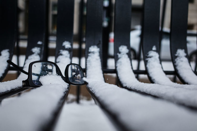 Close-up of a pair of broken reading glasses left on a snowy snow park bench