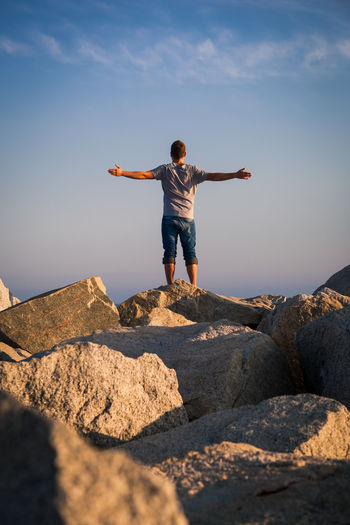 Rear view of man standing on rock against sky