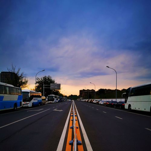 Vehicles on road against sky at sunset