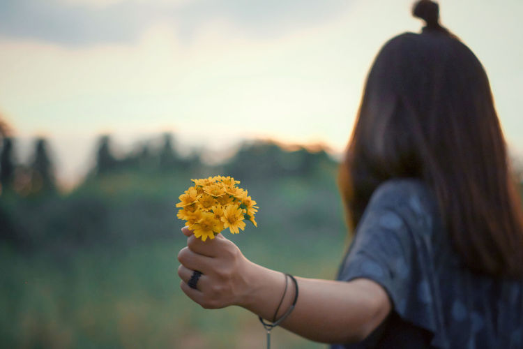 Midsection of woman holding yellow flowering plant during sunset