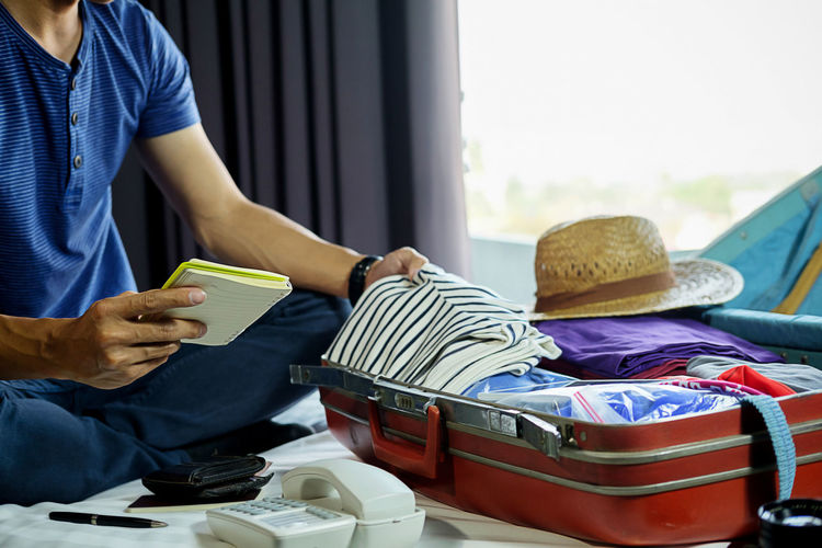 Midsection of man holding checklist and packing suitcase while sitting on bed at home