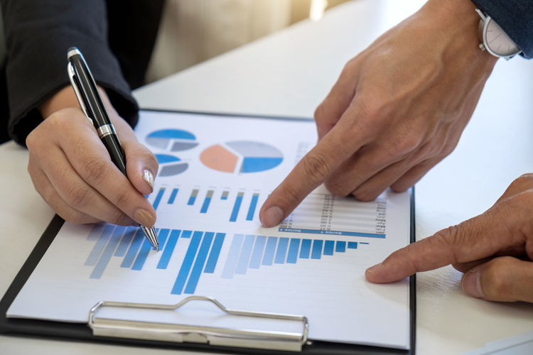 Cropped Hands Of Businessmen Pointing On Graph At Desk