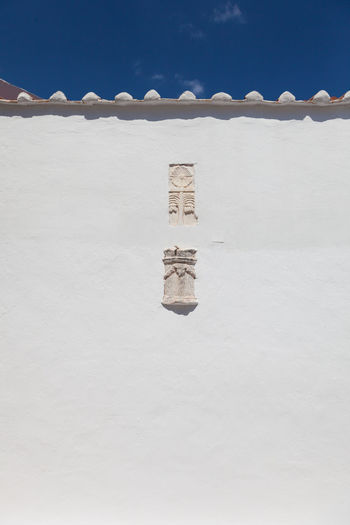 Low angle view of symbol carving on white church wall