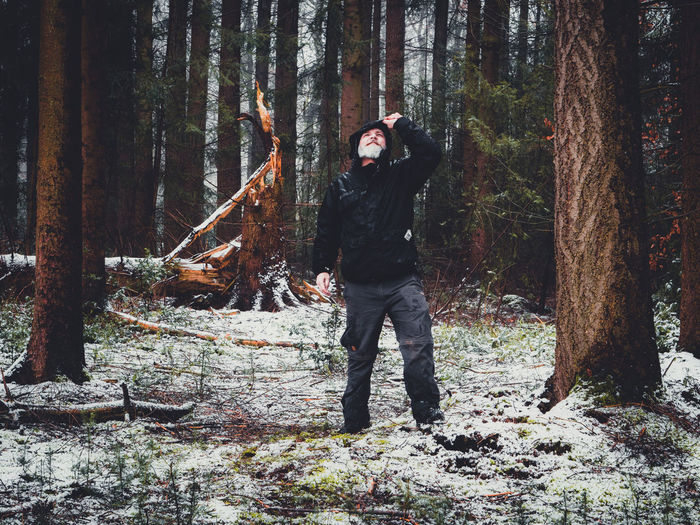 Full length of man standing by trees in forest