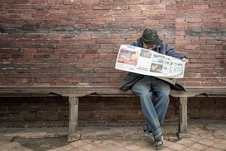 Man holding umbrella against brick wall