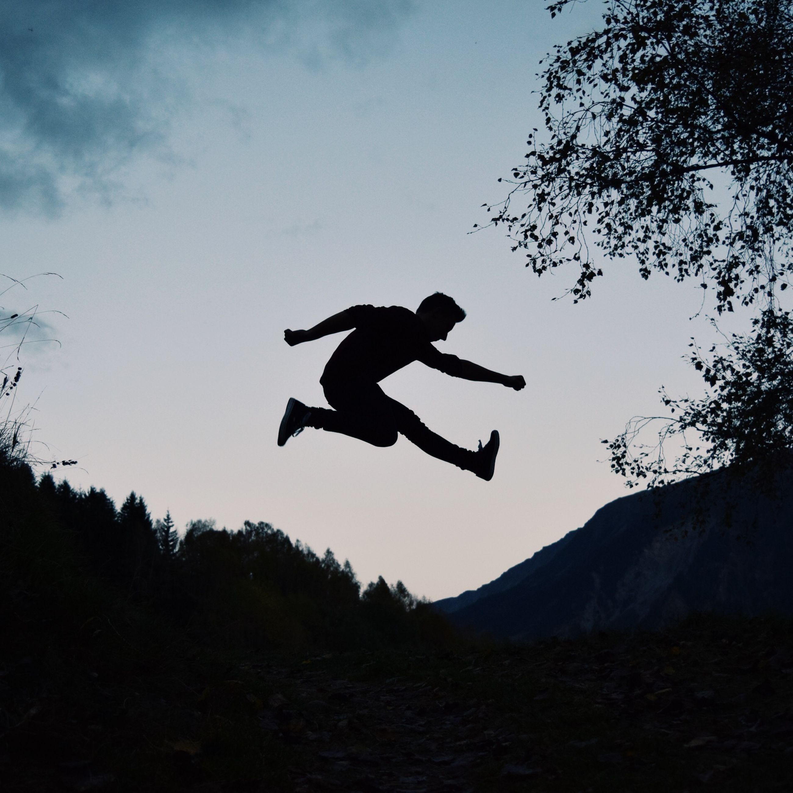 silhouette, mid-air, sky, low angle view, full length, jumping, flying, freedom, leisure activity, mountain, nature, lifestyles, men, side view, outdoors, dusk, arms outstretched, tranquility