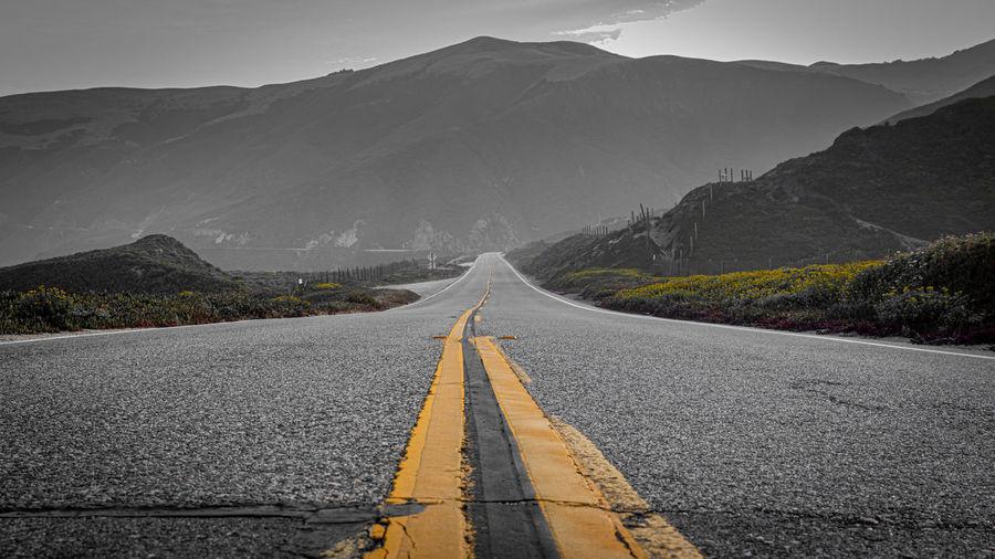 Surface level of empty road leading towards mountain range