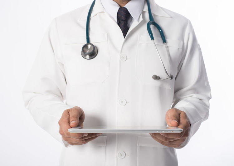 Midsection Of Doctor Holding Digital Tablet Over White Background