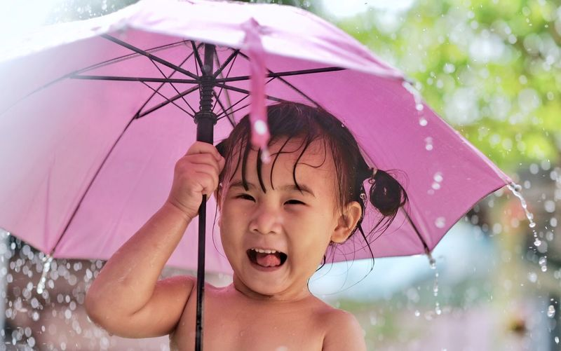 Happy funny child with pink umbrella under shower. Little girl enjoying rainfall in the garden. Selective focus Umbrella Child Childhood Wet Protection One Person Happiness Portrait Front View Security Smiling Emotion Rain Real People Nature Fun Water Innocence Outdoors