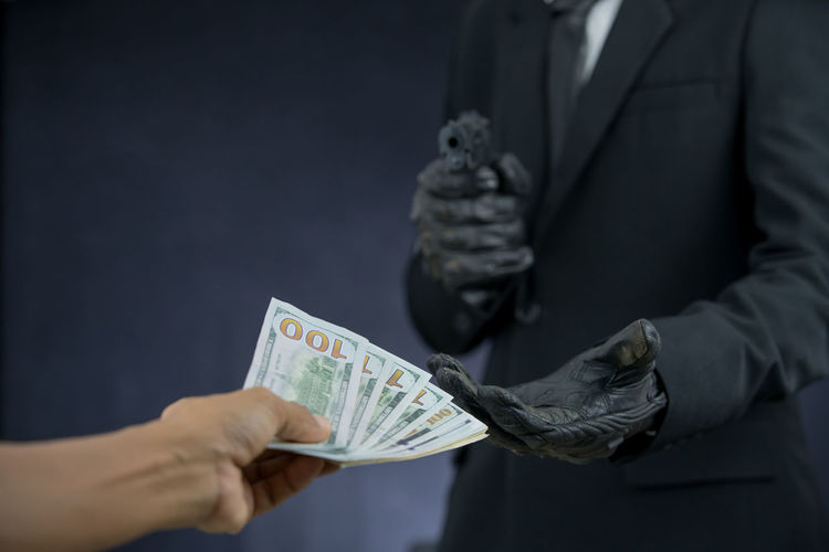 businessman holding gun and robbing dollar banknote from other Crime Gun Banknote Black Background Businessman Currency Dollar Finance Holding Human Body Part Human Hand Paper Currency Rob Savings Studio Shot Two People Wealth