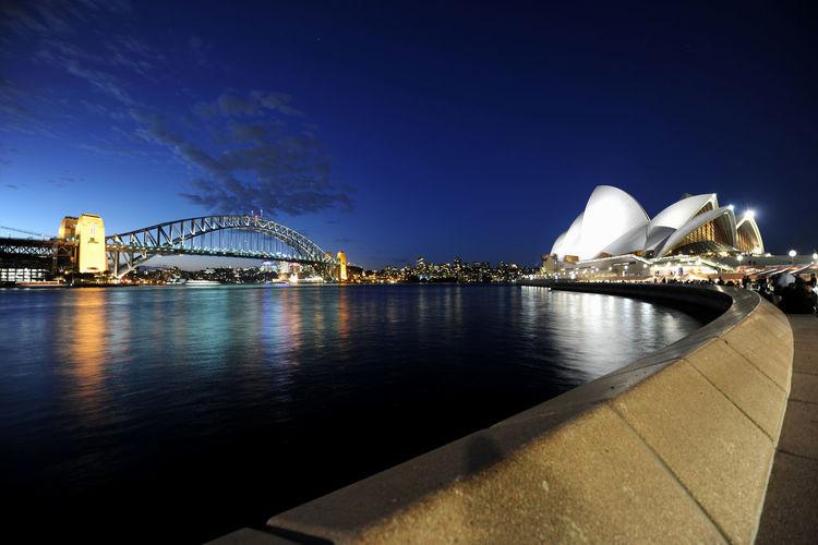 View of bridge over city at night
