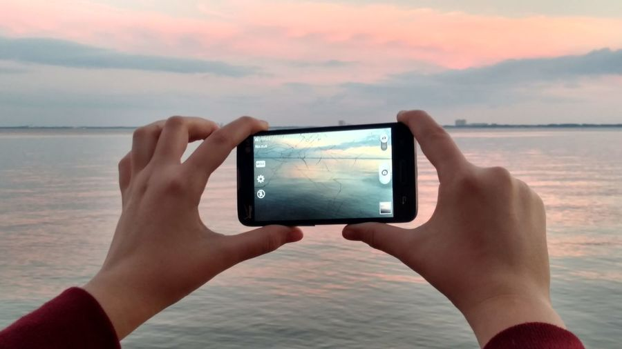 Cropped Hand Of Person Photographing Lake Through Smart Phone Against Sky During Sunset