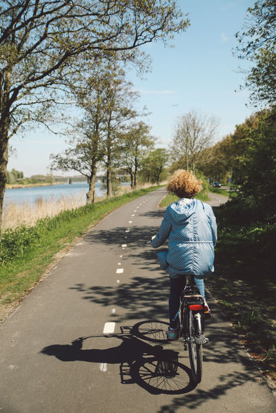 Bicycle Curly Hair Cycling Cycling Helmet Day Full Length Girl Land Vehicle Leisure Activity Mode Of Transport Nature One Person Outdoors Real People Rear View Riding Road Shadow Sky Sunlight The Way Forward Transportation Tree