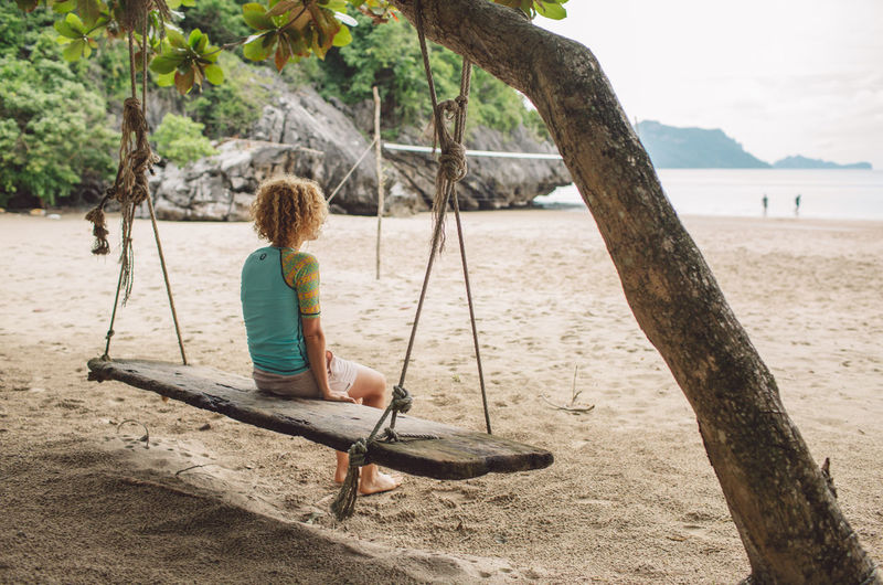 Curly Hair Girl Tree One Person Land Sand Nature Full Length Beach Real People Leisure Activity Water Plant Rear View Sea Sitting Day Lifestyles Casual Clothing Swing Playground Outdoors Rope Swing Hairstyle