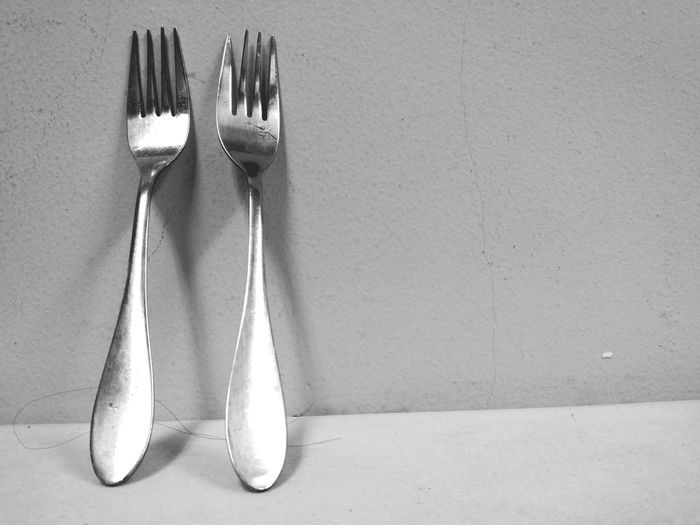 Close-Up Of Forks Against Wall