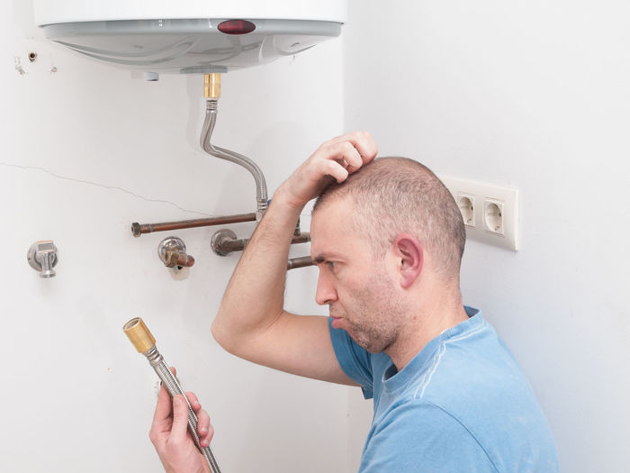 Repairing an electric boiler DIY DIY At Home Doubt Fix  Heater Home Adult DIY Domestic Bathroom Domestic Room Electric Boiler Electric Heater Headshot Holding Home Improvement Home Interior Household Equipment Indoors  Inexperienced Lifestyles Maintenance One Person Real People Repair Repairing