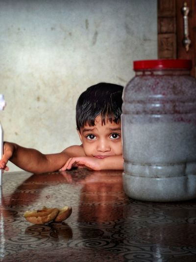 Portrait of smiling boy with drinking water on table