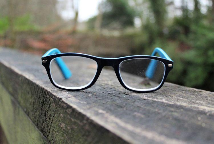 Close-up of eyeglasses on wooden railing