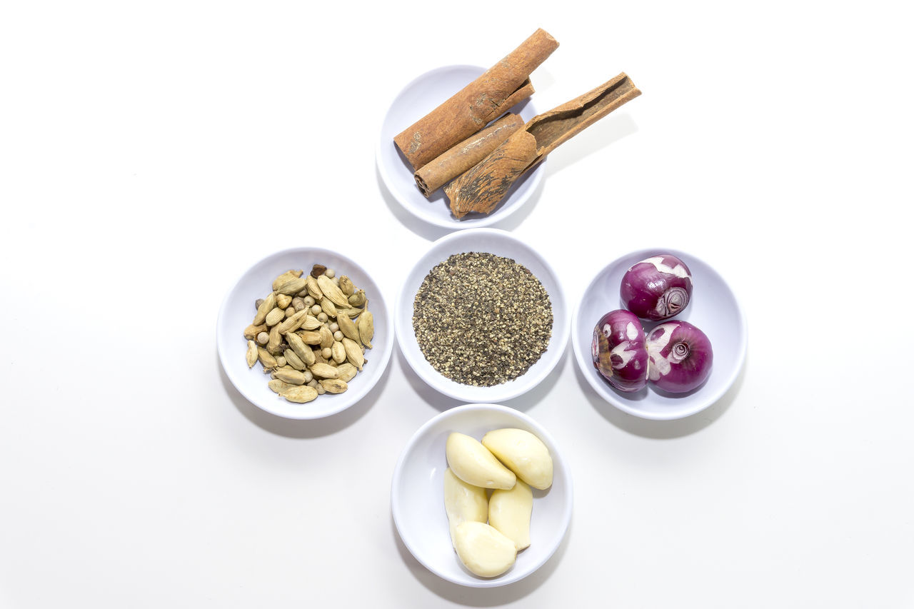 Spices And Vegetables On Wicker Basket On White Background