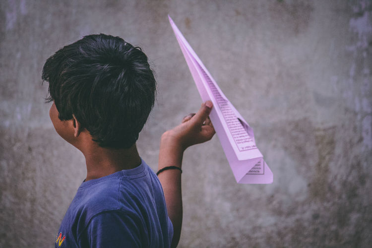Boy holding paper airplane against wall