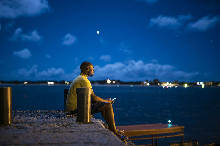 Side view of man sitting on pier by sea at night