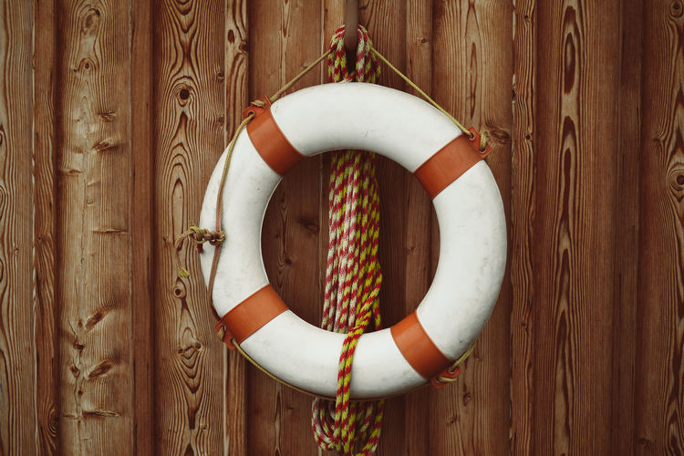Life ring Wood - Material Life Belt Safety Circle Geometric Shape Protection Tubing Security Hanging Shape Rope No People Tube Day Close-up Design Outdoors Tied Up Directly Above Brown Life Ring Beach Lake Swimming