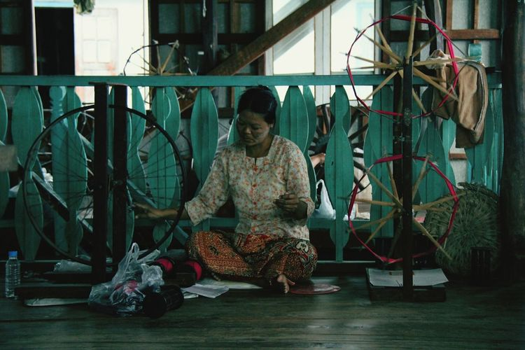 Woman Working On Spinning Wheel At Home