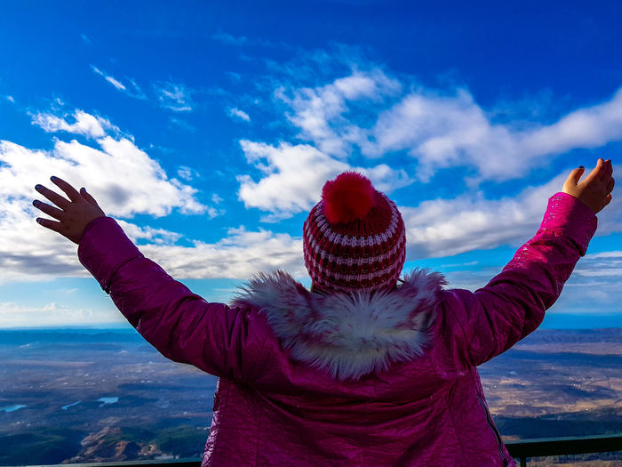 Rear view of girl with arms raised standing on observation point against blue sky