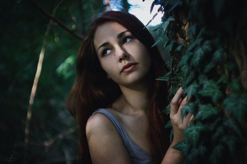 Thoughtful Young Woman Leaning On Tree In Forest