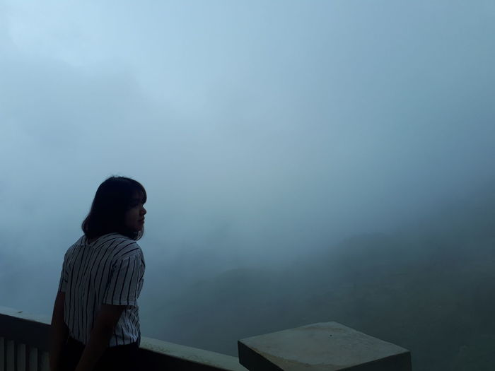 Woman looking at mountain during foggy weather