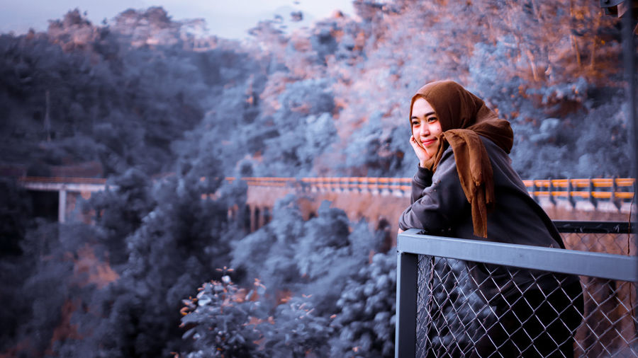 Smiling woman looking away while standing by railing during winter