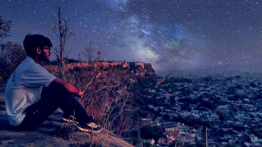 Thoughtful Man Sitting On Cliff By Cityscape Against Starry Sky
