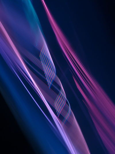 Close-up of light trails over blue background