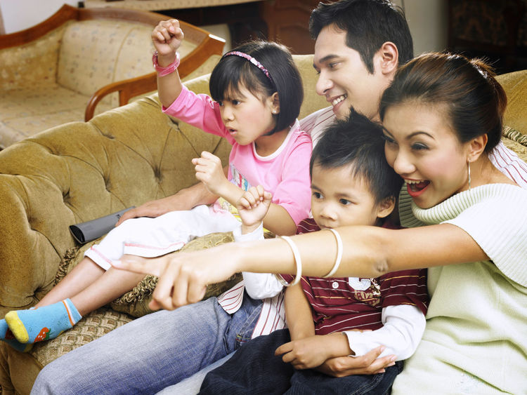parent with two kids at home watching tv Asian Family At Home Family Happiness Happy Love Bonding Cheerful Childhood Elementary Age Enjoying Life Enjoyment Excited Family Family Time Group Of People Leisure Activity Parent With Kids Parenting Real People Simple Life Sitting Smile Togetherness Watching Tv