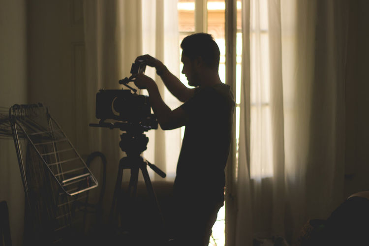 Side view of silhouette man photographing at home